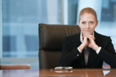 Confident Businesswoman At Conference Table --Portrait of a confident businesswoman sitting at conference table
